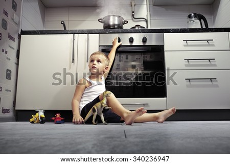 accident prevention. The child unattended playing in the kitchen with a gas stove. - stock photo