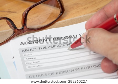 Accident report application form and human hand with pen on brown envelope and eyeglass, business insurance and risk concept; document is mock-up - stock photo
