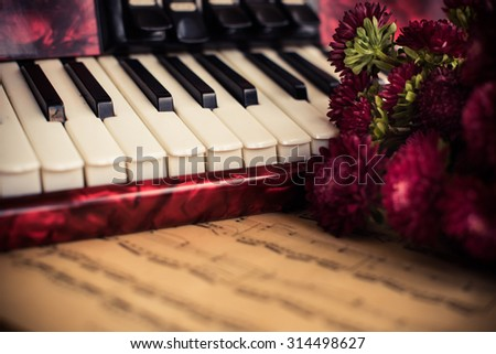 Accordion keys, old notes and a bouquet of flowers, a nostalgic music vintage arrangement - stock photo