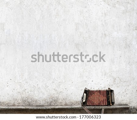 accordion on the bench near the wall background - stock photo