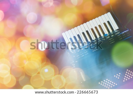 Accordion with color bokeh light in background  - stock photo