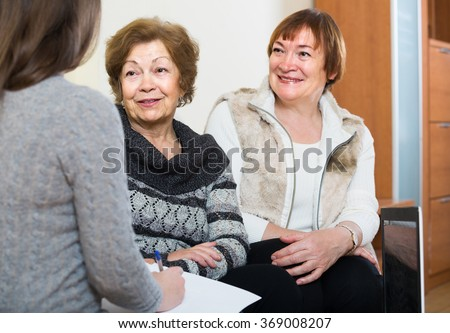 account manager helping smiling elderly women with finances at home - stock photo