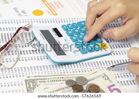 Accountant Checking A Spreadsheet With Calculator and dollars. - stock photo
