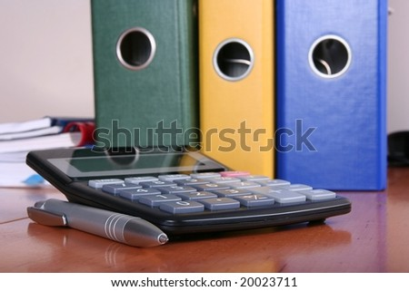 accountant desk with clip folders and calculator - stock photo