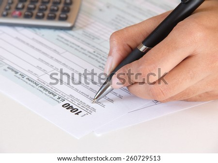Accountant filing federal tax form 1040 - stock photo