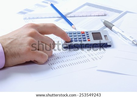 Accountant. Man's hand and calculator. Finance department, accounts, accounting documents. Pens, pencils, papers, ruler and calculator. The man with the calculator. Office worker. Toned image. - stock photo