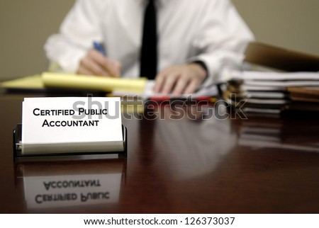 Accountant sitting at desk with stacks of files and business card - stock photo