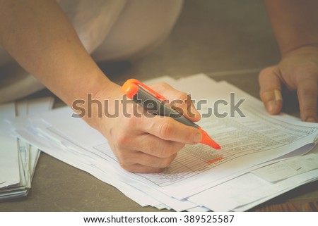 accounting concept : Hand highlighters important number on document . - stock photo