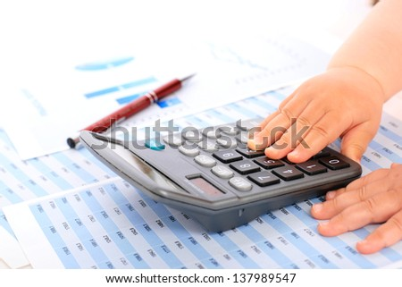 Accounting concept. Kid hands and calculator. - stock photo