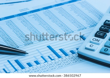Accounting financial banking stock spreadsheet data with pen and calculator in blue  - stock photo