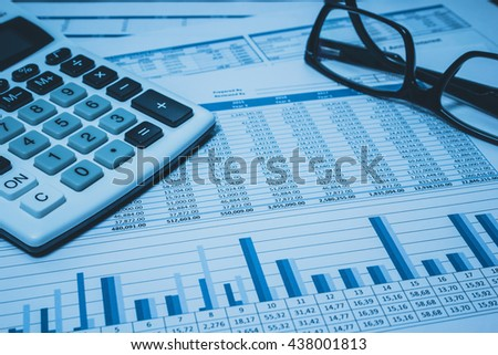Accounting financial banking stock spreadsheet  with accountant  data with glasses and calculator in blue  - stock photo