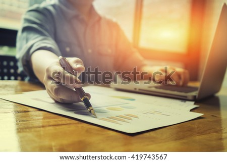 accounting,financial,close up of business man hand working on laptop computer with business graph information diagram on wooden desk as concept,vintage,selective focus - stock photo