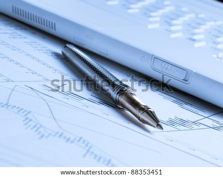 Accounting with pen and laptop on the table - stock photo