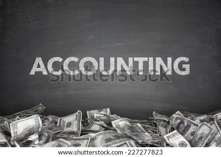 Accounting word on black blackboard with pile of dollars - stock photo
