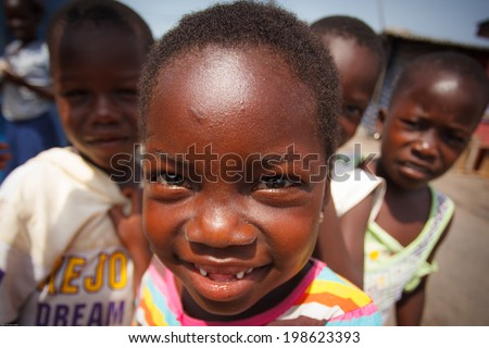 ACCRA, GHANA - MARCH 18: Unidentified African kids greeting to tourists with smiling faces on May 18, 2014 in Teshie community, Accra, Ghana. Teshie is the famous fishing community in Ghana. - stock photo