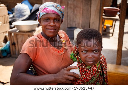 ACCRA, GHANA - MARCH 18: Unidentified African mother and son pose to camera on May 18, 2014 in Teshie community, Accra, Ghana. Teshie is the famous fishing community in Ghana. - stock photo