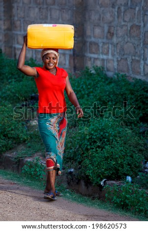 ACCRA, GHANA - MARCH 18: Unidentified African woman carry thing on her head on March 18, 2014 in Accra, Ghana. Carrying things on head is general skill of African girls and women. - stock photo