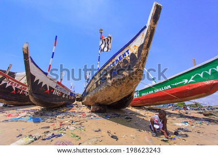 ACCRA, GHANA - MARCH 18: Unidentified Ghanaian boy and native Ghanain style fishing boat on March 18, 2014 in Teshie community, Accra, Ghana. Teshie is the famous fishing community in Ghana. - stock photo