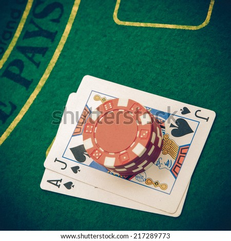 Ace of hearts and black jack with red poker chips - stock photo