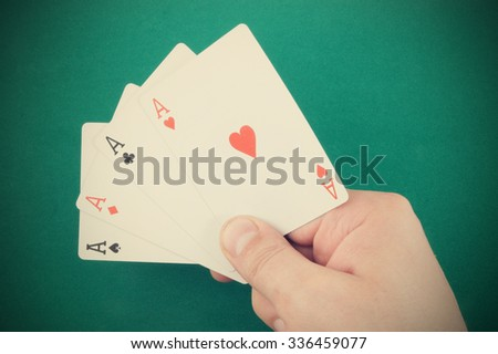 Aces in hand on green table background - stock photo