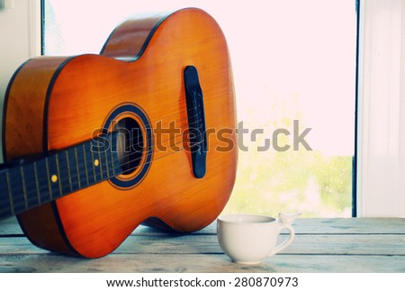 Acoustic guitar and cup of tea next the window with rain drops  - stock photo