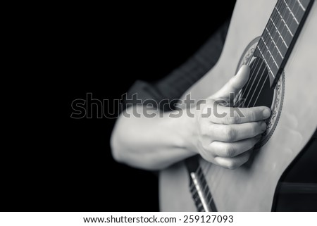 Acoustic guitar detail on black and white - Musician hands playing a classic guitar isolated on a black background - stock photo