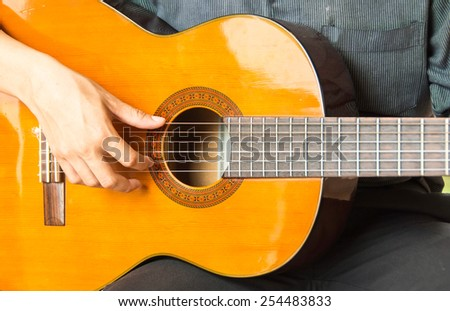Acoustic guitar guitarist playing.Close up of guitarist hand playing acoustic guitar - stock photo