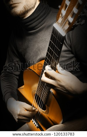Acoustic guitar guitarist playing details. Musical instrument with musician hands. Focus is on the hand with instrument - stock photo