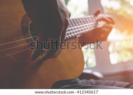 Acoustic guitar guitarist playing. Musical instrument with performer hands. - stock photo