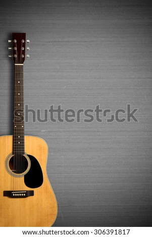 Acoustic guitar is on the gray wall. - stock photo