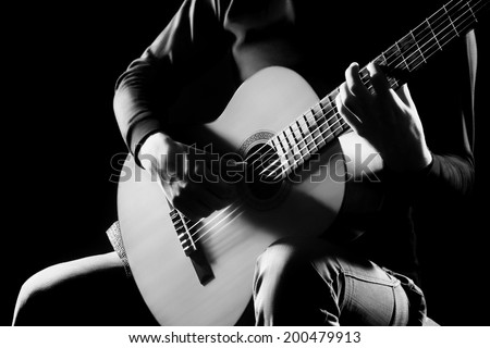 Acoustic guitar music instrument classical guitar in guitarist hands closeup - stock photo