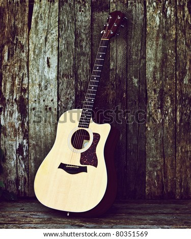 Acoustic guitar on a grunge wood backdrop with copy space. - stock photo