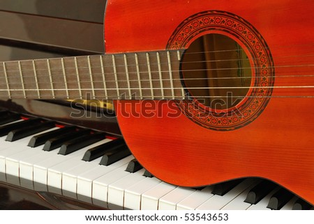 Acoustic guitar on piano keyboard. For concepts like music composition and creativity. - stock photo