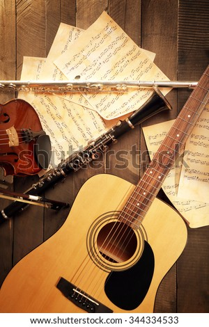 Acoustic guitar, soprano saxophone, violin, flute and note sheets on wooden background - stock photo