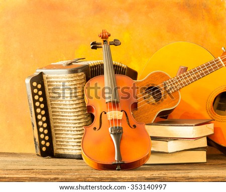Acoustic musical instruments guitar ukulele violin and accordion with vintage book lay on fine painted floor and backdrop for wall web interior decoration still life style - stock photo