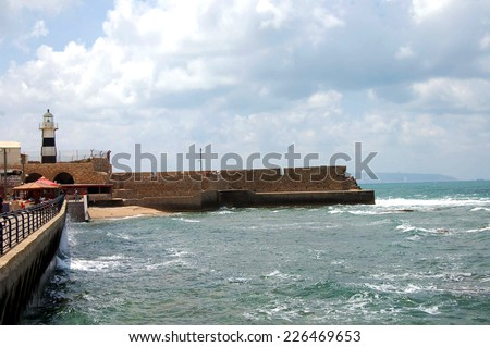 Acre (or Akko) Lighthouse in Israel watches over Haifa Bay on the Mediterranean Coast. - stock photo