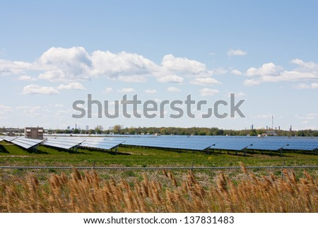 Acres of farmland covered with solar panels, produce energy from the sun at this large scale solar farm in Sarnia Ontario, Canada. - stock photo