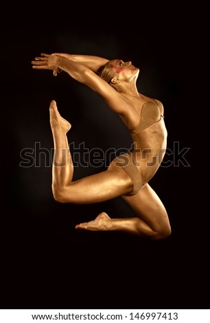 acrobat dancer toned in gold  jumping over black background - stock photo
