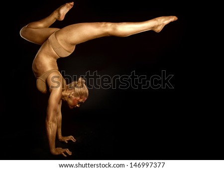 acrobat dancer toned in gold  posing over black background - stock photo
