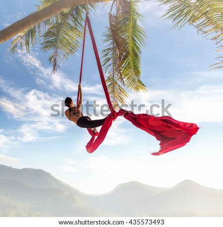 Acrobatic movement with performing on aerial silks or ribbons tissue - stock photo