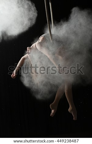 Acrobatic woman doing element on aerial hoop with sprinkled flour - stock photo