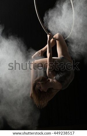 Acrobatic woman doing trick on aerial hoop with sprinkled flour - stock photo