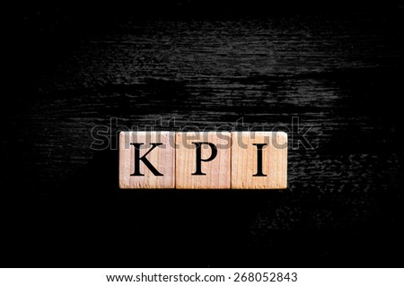 Acronym KPI - key performance indicator. Wooden small cubes with letters isolated on black background with copy space available. Business Concept image. - stock photo