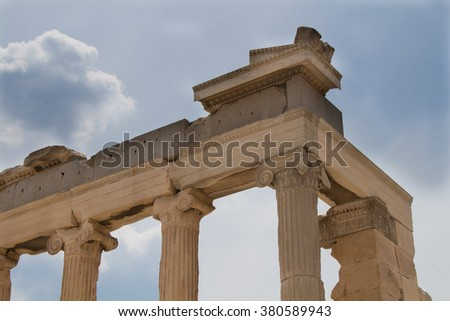 Acropolis, details of the architecture, Greece Antique ruins of a building at Acropolis in greek capital Athens. Columns and the edge of the roof. Cloudy sky in the background. - stock photo