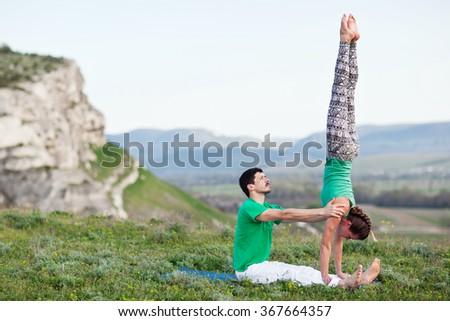 Acroyoga - Balancing on Feet. Couple practicing acroyoga in mountains at sunrise. Crimea - stock photo