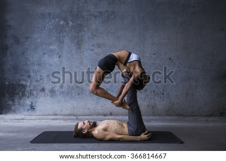 Acroyoga practice, man on woman on a urban background - stock photo