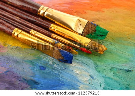 acrylic paint and brushes on wooden palette - stock photo