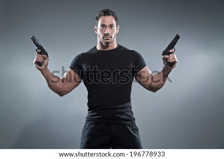 Action hero muscled man holding two guns. Wearing black t-shirt and pants. Studio shot against grey. - stock photo