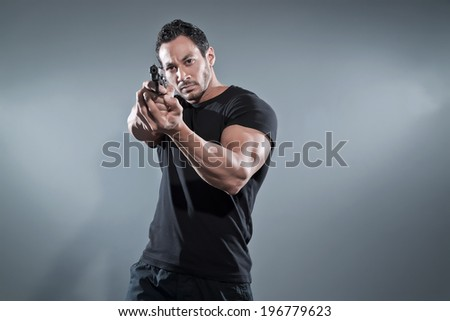 Action hero muscled man shooting with gun. Wearing black t-shirt and pants. Studio shot against grey. - stock photo
