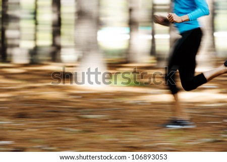 Action motion shot of runner training in forest with blur to show speed and sprinting. - stock photo